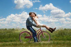 Woman and man on a bike, outside on a daylight.
