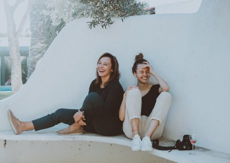 Two women sitting on a white bench