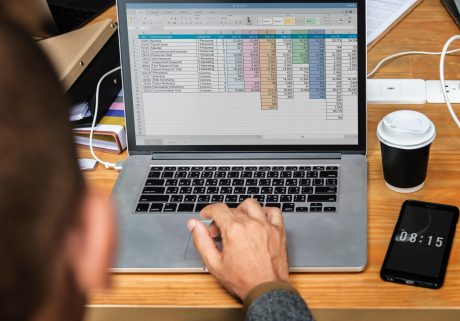 A person sitting in front of the monitor where spreadsheet for planning commercial relocation is opened