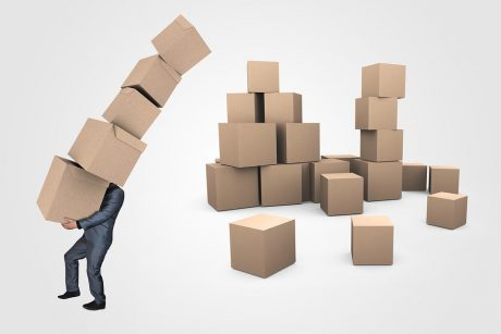 A businessman carrying a lot of cardboard boxes.