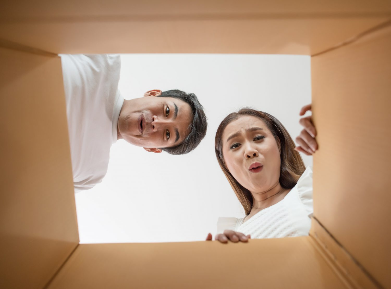 couple stare into a box and unpack after a move