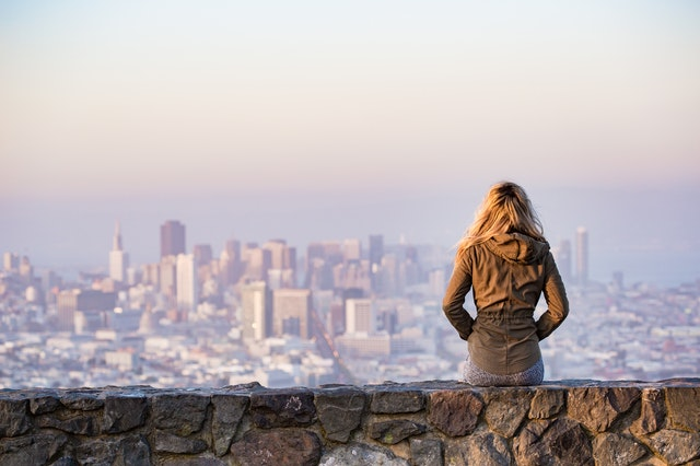 Woman sitting on rock platform viewing the skyline of San Francisco, CA