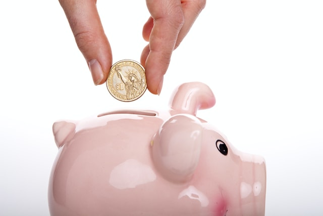 A person putting a coin into a piggy bank after success in organizing a cost=effective interstate move.