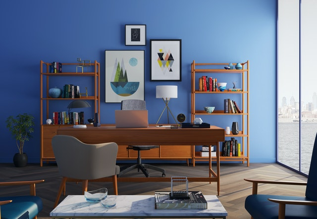 A room painted in blue with décor details on shelves.