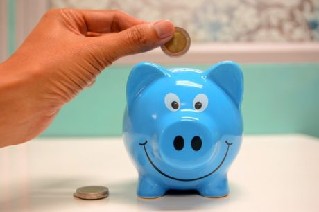 A person is putting a coin into a piggy bank, since saving some money in advance is the best way to settle in trouble-free if you are a newcomer in Los Angeles.