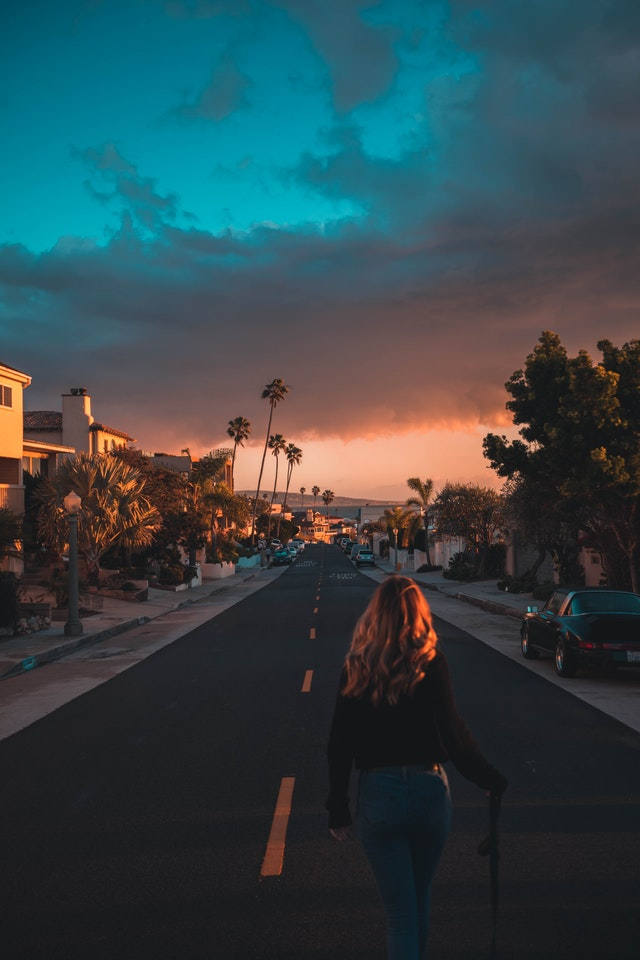 A young girl is walking down one of the LA streets during the sunset.