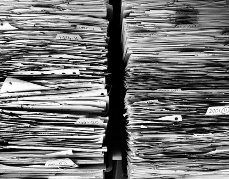 Two piles of documents symbolizing all the papers you need when shipping goods from Saudi Arabia.