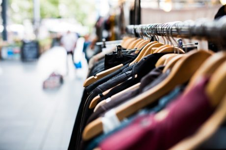 clothing hanging on a rack during a sale organized to overcome one of the most common challenges of moving - declutter and lack of finances.