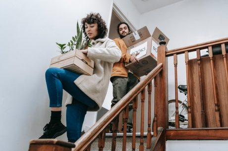 Couple going down stairs with boxes